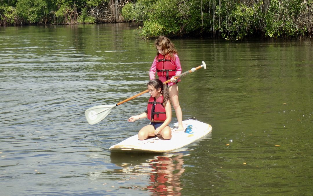 Sisters sharing a Stand Up Paddle Board